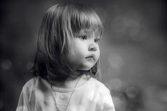 Verticale noire et blanche d'une petite fille sérieuse Photographie stock