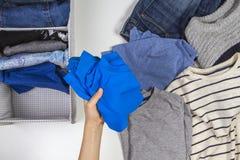Verticale opslag van kleding, het opruimen, ruimte het schoonmaken concept Handen die en jonge geitjeskleren in mand opruimen sor royalty-vrije stock fotografie