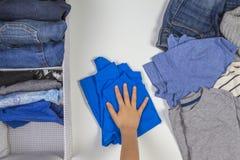 Verticale opslag van kleding, het opruimen, ruimte het schoonmaken concept Handen die en jonge geitjeskleren in mand opruimen sor royalty-vrije stock foto's