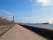 Verticale perspectiefmening langs de voetpromenade in Blackpool met een mening van de stadstoren en pijler in de afstand stock fotografie