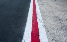 Verticale rode en witte lijnen op donker grijs asfalt Stock Afbeelding