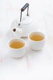 Verticale theepot en koppen van groene thee op een witte houten lijst, Stock Foto