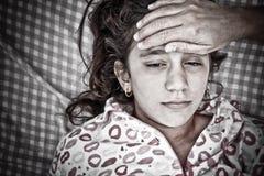 Verticale triste d'une petite malade de fille avec la fièvre Photos stock