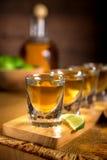 Verticale vicino su dei colpi di tequila raggruppati insieme ad una bottiglia ed alle calce tagliate su una superficie di legno Fotografie Stock Libere da Diritti