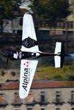 Verticale volante dell'aereo di Michael Goulian contro il fondo delle costruzioni Fotografia Stock