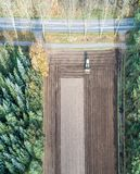 Vertically aligned aerial photograph of a field area worked by a. Vertically aligned aerial photograph taken with the drone of an area of arable land treated by Royalty Free Stock Photos