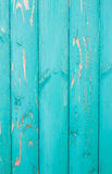 Vertically located colored distressed turquoise paint boards, old fence. Distressed painted with turquoise paint boards, old fence Stock Photos