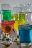 Verticeal group of glasses with colorful water. Multi colored liquid in pretty glasses with iceon table stock photography