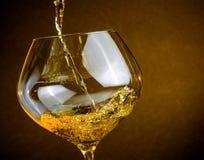 Vertiendo el vino blanco en un vidrio con el espacio para el texto, caliente la atmósfera Imagen de archivo
