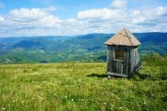 Vertiente de madera abandonada, pequeña casa, en un prado verde, horizonte azul, montañas, Ucrania Foto de archivo libre de regalías