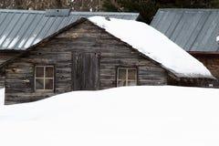 Vertiente vieja detrás de un banco de la nieve Fotos de archivo libres de regalías
