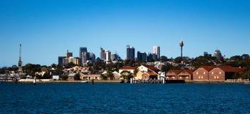Vertientes de las casas, del muelle y del barco de Harbourside de la ciudad en Sydney Harbour con horizonte de la ciudad CBD en f fotografía de archivo