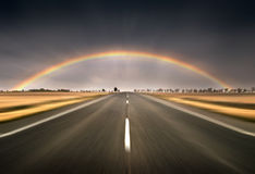 Vertigo. Composition created with two photos stitched, with a road leading to the horizon on the foreground and a rainbow on the upper side of the image Royalty Free Stock Photo