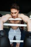 Vertikal bild av den trötta boxaren som kopplar av i boxningsring Arkivbilder