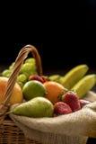 Vertikal Closeupdetalj på en korg mycket av frukt på en mörk bakgrund arkivbilder