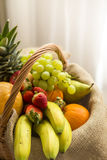 Vertikal detalj av en korg mycket av frukter på en ljus bakgrund - hög tangent royaltyfri bild