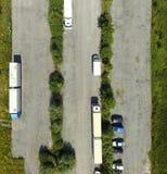 Vertikal flyg- sikt av en nästan tom asfalterad grå parkeringsplats med två lastbilar och bilar royaltyfria bilder