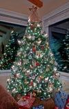 Vertikal högväxt dekorerad julgran inomhus Royaltyfri Bild