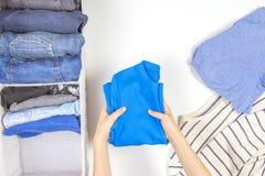 Vertikal lagring av att bekläda som ordnar, rengörande begrepp för rum Händer som ordnar och sorterar ungekläder i korg royaltyfri bild