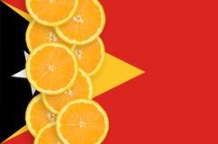 Vertikal rad för Östtimor flagga- och citrusfruktskivor arkivfoto