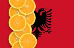 Vertikal rad för Albanien flagga- och citrusfruktskivor royaltyfri foto