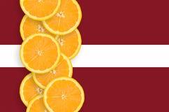 Vertikal rad för Lettland flagga- och citrusfruktskivor arkivfoto