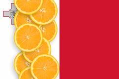 Vertikal rad för Malta flagga- och citrusfruktskivor arkivbilder