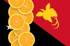 Vertikal rad för Papua Nya Guinea flagga- och citrusfruktskivor royaltyfria foton