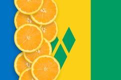 Vertikal rad för Saint Vincent och Grenadinerna flagga- och citrusfruktskivor fotografering för bildbyråer