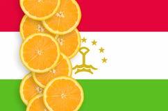 Vertikal rad för Tadzjikistan flagga- och citrusfruktskivor arkivbilder