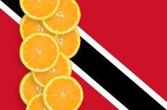 Vertikal rad för Trinidad och Tobago flagga- och citrusfruktskivor royaltyfri foto