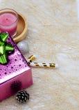 Vertikal sida för julbakgrunder med den rosa gåvaasken och candl royaltyfri foto