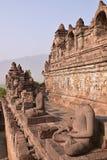 Vertikal sidosikt av en rad av statyer utan huvud på Borobudur Arkivbild