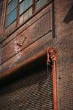 Vertikal stads- tegelstenbyggnad med säkerhetsporten Royaltyfri Foto