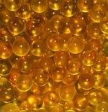 Vertikal textur av den runda genomskinliga guld- gulingen klumpa ihop sig FiskFISKROM, fiskolja Royaltyfri Fotografi