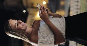 Vertikal video Attraktiv ung kvinna som använder smartphoneanseende på gatan av nattstaden som lyckligt reagerar till meddelandet arkivfilmer