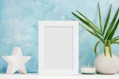 Vertikal vit fotoramåtlöje upp med växter i vasen, keramisk dekor på hylla Skandinavisk stil arkivbilder