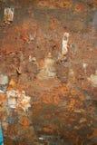 Vertikale Ansicht der rostigen verwitterten Metallwand mit Stückchen von Papier a Lizenzfreie Stockfotos