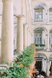 Vertikale Ansicht des alten Balkons voll der orange Blumen Lizenzfreies Stockbild