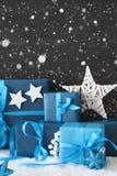 Vertikale blaue Weihnachtsgeschenke, schwarze Zement-Wand, Schnee, Schneeflocken Stockfotografie