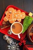 Vertikale Draufsicht der Lebkuchenmänner mit Kaffee auf rotem Teller lizenzfreie stockfotografie