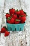 Vertikale Erdbeeren in einem Grünbuchkarton auf weißem Holz lizenzfreies stockbild