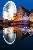 Vertikale Nachtansicht für Riesenrad mit Wasserreflexion Stockfotos