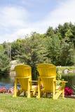 Vertikale Paare gelber muskoka Stühle am See Lizenzfreie Stockfotografie