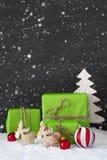 Vertikale rote und grüne Weihnachtsdekoration, schwarze Zement-Wand, Schneeflocken Stockfotografie