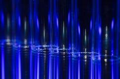 Vertikale Streifen des blauen und weißen Lichtes, das einen faszinierenden Hintergrund bildet Lizenzfreies Stockfoto