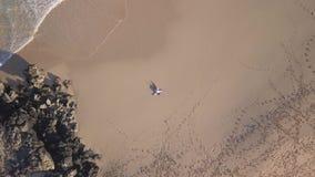 Vertikale Vogelperspektive eines Mädchens, das in einem einsamen Strand liegt stock video footage