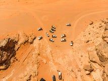Vertikale Vogelperspektive eines Satzes Geländefahrzeuge mit Touristen in der Wadi Rum-Wüste in Jordanien, genommen mit Brummen lizenzfreie stockfotografie