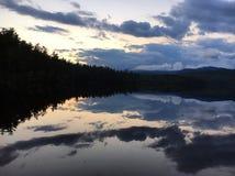 Vertikaler Aufbau der Bäume Bushers und Moutain, die im ruhigen See während des Sonnenuntergangs sich reflektieren stockbilder