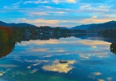 Vertikaler Aufbau der Bäume Bushers und Moutain, die im ruhigen See während des Sonnenuntergangs sich reflektieren Lizenzfreies Stockfoto